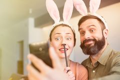 Young loving couple making selfie on mobile phone with pink rabbit ears on head. Happy family preparing for Easter. Young loving couple making selfie on mobile stock photo