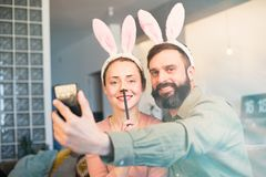 Young loving couple making selfie on mobile phone with pink rabbit ears on head. Happy family preparing for Easter. Young loving couple making selfie on mobile stock image