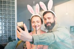 Young loving couple making selfie on mobile phone with pink rabbit ears on head. Happy family preparing for Easter. Young loving couple making selfie on mobile stock images