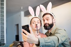 Young loving couple making selfie on mobile phone with pink rabbit ears on head. Happy family preparing for Easter. Young loving couple making selfie on mobile royalty free stock image