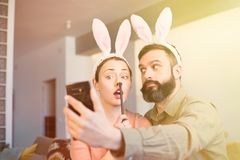 Young loving couple making selfie on mobile phone with pink rabbit ears on head. Happy family preparing for Easter. Flare stock photo