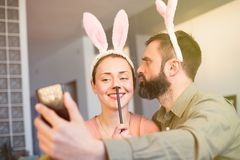 Young loving couple making selfie on mobile phone with pink rabbit ears on head. Happy family preparing for Easter. Flares stock image