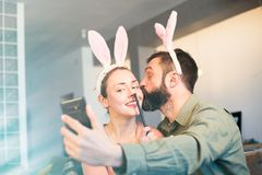Young loving couple making selfie on mobile phone with pink rabbit ears on head. Happy family preparing for Easter. Young loving couple making selfie on mobile royalty free stock photography