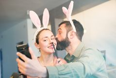 Young loving couple making selfie on mobile phone with pink rabbit ears on head. Happy family preparing for Easter. Young loving couple making selfie on mobile stock photography