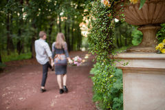 Young loving couple outdoor, holding hands and leaving the path in beautiful garden. Natural light, defocused. Stock Photos