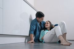 Young loving couple on the parquet floor in white kitchen interior sitting and smiling at each other royalty free stock image