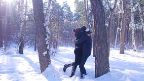 A young and loving couple is playing near the tree in the winter forest stock video