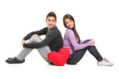 Young loving couple and a red heart shaped pillow Stock Photos