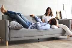 Free Young Loving Couple Relaxing On Sofa Together, Husband Lying On Wife Legs Resting On Couch Stock Photography - 195471402