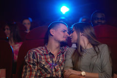 Young loving couple sharing romantic moment at the cinema. Low angle shot of a young loving couple sharing romantic moment on a date at the cinema touching noses Royalty Free Stock Images