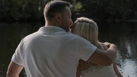 Young loving couple sit on the pier near the river and kiss. Back view. Young loving couple sit on the pier near the river and kiss. A man hugs a woman. Back stock footage