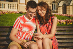 Young loving couple sitting on the bench in the center of the city, laughing, listening to music and having fun with smartphone Stock Photography