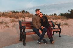 Young loving couple sitting on benches near the sea shore in autumn. Stock Images
