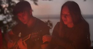 Young loving couple sitting by the bonfire and playing guitar in forest. Close up stock footage