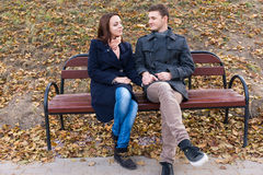 Young loving couple sitting chatting on a bench Royalty Free Stock Image