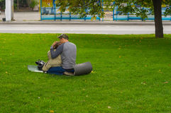 Young loving couple sitting on a ground pad on green lawn on Dnepr river embankment. DNEPR, UKRAINE - SEPTEMBER 25, 2016:Young loving couple sitting on a ground royalty free stock images