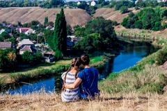 Young loving couple sitting in hug on the top of a hill with wonderful view of the river Stock Photos