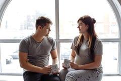 Young loving couple sitting near window royalty free stock photo