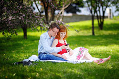 Young loving couple sitting at park on the grass in spring Royalty Free Stock Photos