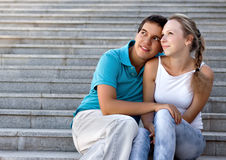Young loving couple sitting on stairs Stock Images