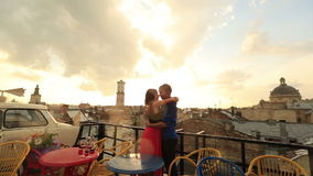 Young loving couple softly kissing on the rooftop cafe with ancient city view while raining. Romantic sunset with sky in