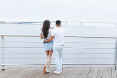 Young loving couple stands with their backs on sea promenade. Lifestyle Concept royalty free stock photos
