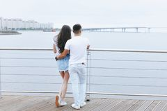 Young loving couple stands with their backs on sea promenade. Lifestyle Concept royalty free stock images