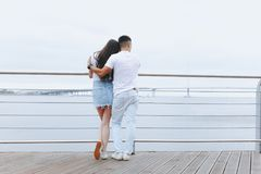 Young loving couple stands with their backs on sea promenade. Lifestyle Concept stock photo