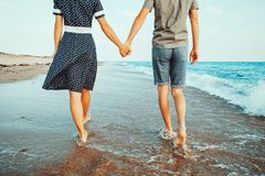Loving couple walking on shore. Young loving couple walking on shore on sea waves and holding hands, beach summer vacations stock photos