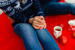Young loving couple warm sweaters and jeans, hugging, sitting on a red blanket. Boyfriend and girlfriend traveling lifestyle, tran. Quility and contemplation on stock images