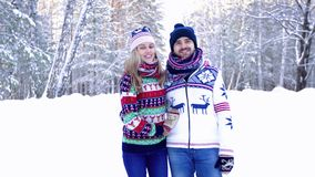 Young loving couple wearing bright winter clothes walking in the snowbound forest stock video footage