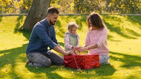 Young loving family trying to undo the ribbon of birthday present stock video footage