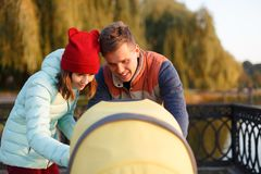 A young loving family walks by the lake with a stroller. Smiling parents couple with baby pram in autumn park look into cariage. L Stock Photography