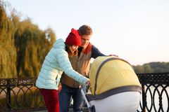 A young loving family walks by the lake with a stroller. Smiling parents couple with baby pram in autumn park look into cariage. L Royalty Free Stock Images