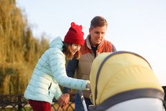 A young loving family walks by the lake with a stroller. Smiling parents couple with baby pram in autumn park look into cariage. L Royalty Free Stock Photography