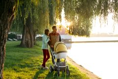 A young loving family walks by the lake with a stroller. Smiling parents couple with baby pram in autumn park. Love, parenthood, f Stock Images