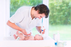 Young loving father changing diaper of newborn son royalty free stock photography