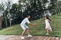Sincere joy. Young loving father keeping arms outstretched while his smiling daughter running to him outdoors stock photos