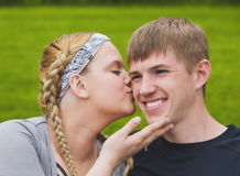 Young loving girl kissing her boyfriend on cheek Stock Image
