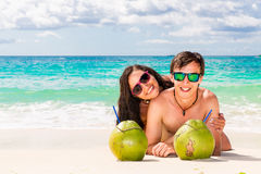 Young loving happy couple have fun on tropical beach, with cocon. Uts. Summer vacation concept Royalty Free Stock Photos