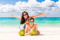 Young loving happy couple have fun on tropical beach, with cocon. Uts. Summer vacation concept Royalty Free Stock Images