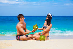 Young loving happy couple on tropical beach, with coconuts. The sea in the background Royalty Free Stock Photography