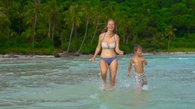 Young loving mother and her little son playing on the beach stock footage