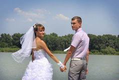 Young loving newlyweds walking on riverside Royalty Free Stock Photos
