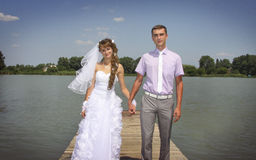 Young loving newlyweds walking on riverside. Young happy newlyweds walking and posing on a riverside Royalty Free Stock Photos