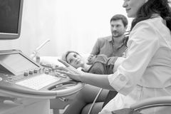 Young loving pregnant couple visiting doctor together monochrome. Black and white shot of a happy pregnant couple watching doctor performing ultrasound scanning Stock Image