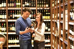 Young lucky couple shopping for red wine in the supermarket. Closeup Stock Photography