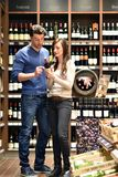 Young lucky couple shopping for wine in the supermarket. Closeup Stock Photo