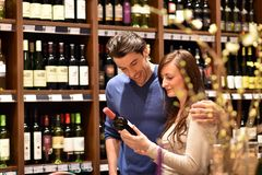 Young lucky couple shopping for wine in the supermarket. Closeup Royalty Free Stock Images