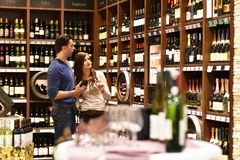 Young lucky couple shopping for wine in the supermarket. Closeup Stock Photos